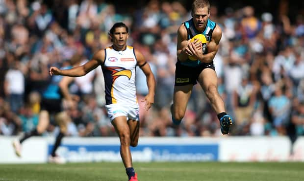 Kane Cornes leaps for a chest mark as the Power open their NAB Challenge account in Norwood