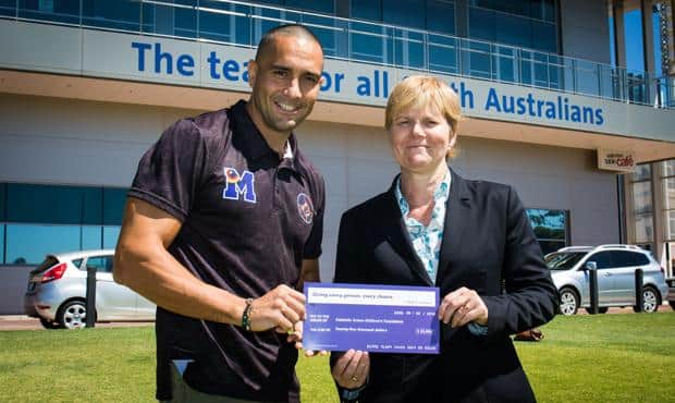 Andrew McLeod accepts a cheque for $25,000 on behalf of the Adelaide Crows Children's Foundation from MAX Employment Director Fiona Lamb