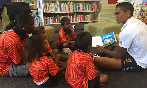 Jermaine Miller-Lewis reads to children from the Milikapiti School.