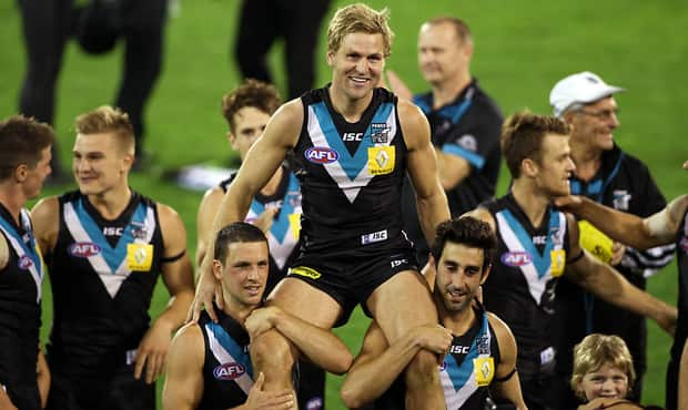 SALUTE: Kane Cornes is chaired off by teammates after his 250th game in 2013. He will play his 300th and final game against Richmond on May 24.