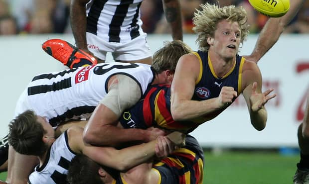 Rory Sloane of the Crows tackled by Lachlan Keeffe and Tom Langdon of the Magpies during the 2014 AFL Round 09 match between the Adelaide Crows and the Collingwood Magpies at Adelaide Oval, Adelaide on May 15, 2014. (Photo: AFL Media)