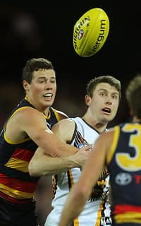Luke Brown of the Crows tackles Liam Shiels of the Hawks during the 2014 AFL Round 17 match between the Adelaide Crows and the Hawthorn Hawks at Adelaide Oval, Adelaide on July 11, 2014. (Photo: James Elsby/AFL Media)