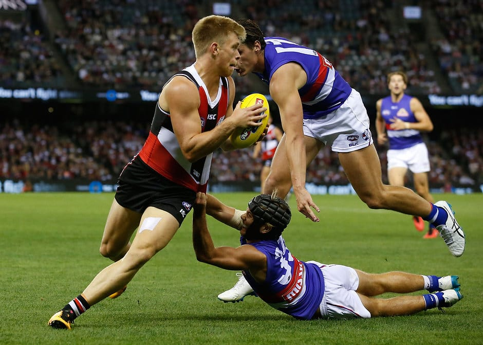 MELBOURNE, AUSTRALIA - APRIL 2: Sebastian Ross of the Saints is tackled by Caleb Daniel and Tom Boyd of the Bulldogs (top) during the 2016 AFL Round 02 match between the St Kilda Saints and the Western Bulldogs at Etihad Stadium, Melbourne on April 2, 2016. (Photo by Michael Willson/AFL Media)