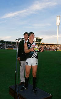 Vice-captain Brayden Lyle lifts the first Showdown trophy at Football Park in lieu of the injured captain Gavin Wanganeen.