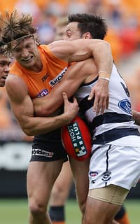 Giant Rhys Palmer is tackled by Geelong's Jimmy Bartel