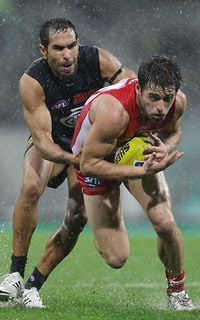 Carlton's Eddie Betts tackles Swan Nick Smith at a soaking SCG on Friday night