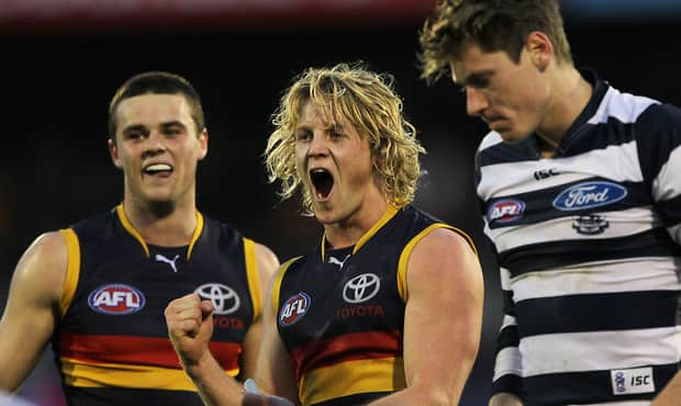 Brad Crouch and Rory Sloane of the Crows celebrate their win with Mark Blicavs of the Cats in front during the 2013 AFL Round 17 match between the Adelaide Crows and the Geelong Cats at AAMI Stadium, Adelaide on July 21, 2013. (Photo: James Elsby/AFL Media)