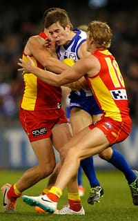 Ryan Bastinac is caught in a Suns sandwich at Etihad Stadium