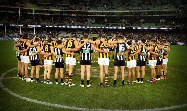 MELBOURNE, AUSTRALIA - JULY 3: Collingwood and Hawthorn players link arm in arm in memory of the death of Adelaide Crows Coach Phil Walsh during the 2015 AFL round 14 match between the Collingwood Magpies and the Hawthorn Hawks at the Melbourne Cricket Ground, Melbourne, Australia on July 3, 2015. (Photo by Justine Walker/AFL Media)