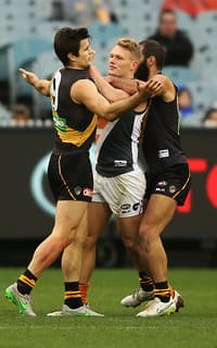 Trent Cotchin comes to grips with Adam Treloar at the MCG as the Tigers triumph