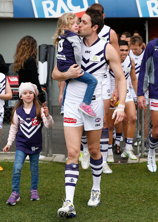 LAUNCESTON, AUSTRALIA - JULY 12: Luke McPharlin of the Dockers runs onto the field for his 250th match with his children during the 2015 AFL round 15 match between the Hawthorn Hawks and the Fremantle Dockers at Aurora Stadium, Launceston, Australia on July 12, 2015. (Photo by Michael Willson/AFL Media)