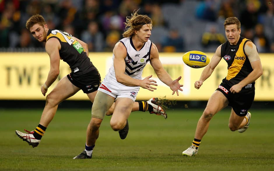 MELBOURNE, AUSTRALIA - JULY 25: Nat Fyfe of the Dockers in action ahead of Anthony Miles (left) and Kane Lambert of the Tigers during the 2015 AFL round 17 match between the Richmond Tigers and the Fremantle Dockers at the Melbourne Cricket Ground, Melbourne, Australia on July 25, 2015. (Photo by Adam Trafford/AFL Media)