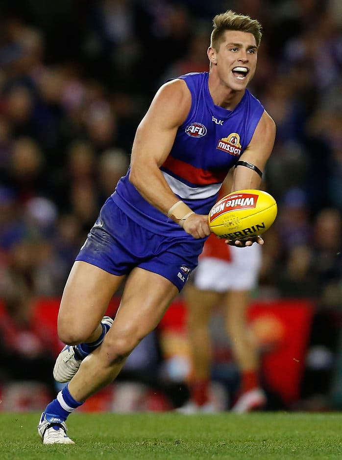 MELBOURNE, AUSTRALIA - AUGUST 16: Michael Talia of the Bulldogs handpasses the ball during the 2015 AFL round 20 match between the Western Bulldogs and the Melbourne Demons at Etihad Stadium, Melbourne, Australia on August 16, 2015. (Photo by Adam Trafford/AFL Media)