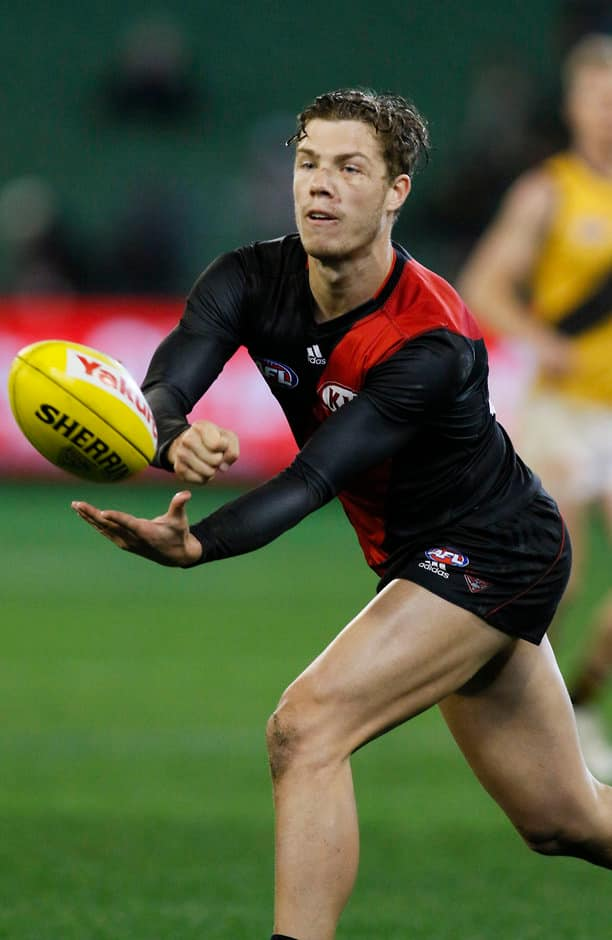 MELBOURNE, AUSTRALIA - AUGUST 29: Essendon's Jake Melksham handballs during the 2015 AFL round 22 match between the Essendon Bombers and the Richmond Tigers at the Melbourne Cricket Ground, Melbourne, Australia on August 29, 2015. (Photo by Greg Ford/AFL Media)