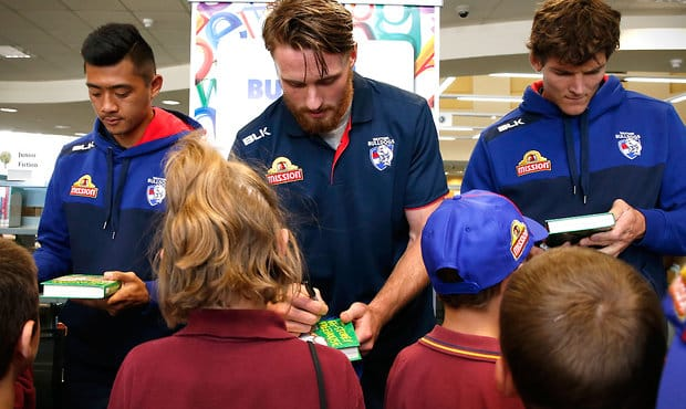 BALLARAT, AUSTRALIA - FEBRUARY 16: (L-R) Lin Jong, Jordan Roughead and Will Minson of the Bulldogs sign autographs during the Western Bulldogs Community Camp at the Ballarat Library in Ballarat, Australia on February 16, 2016. (Photo by Adam Trafford/AFL Media)