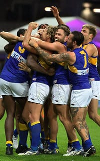 Eagles players mob Nic Naitanui after his match-winning goal against the Giants