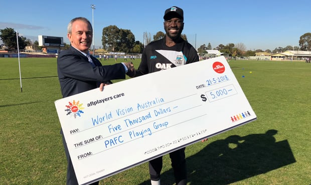 Power player Emmanuel Irra hands over the cheque to  Chair of the World Vision Australia board Shannon Adams.