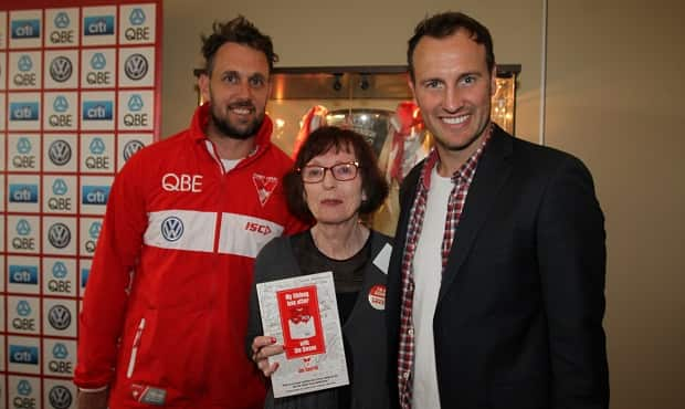 Author Jan Courtin poses with 2005 premiership stars Nick Davis and Jude Bolton.