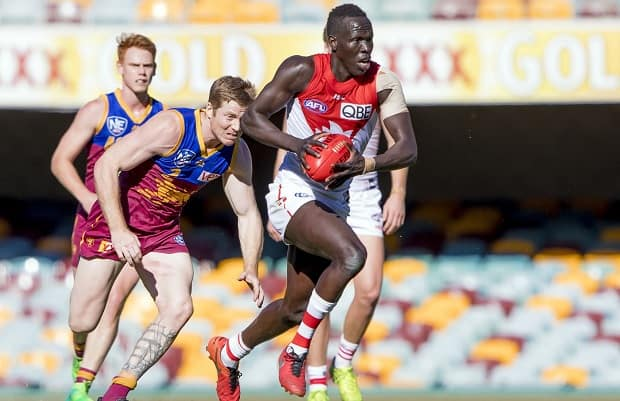 Aliir Aliir streams away from his Brisbane opponent during an earlier meeting between these two sides this year.