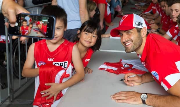 Josh Kennedy poses for a photo with young Swans fans during Fan Day.