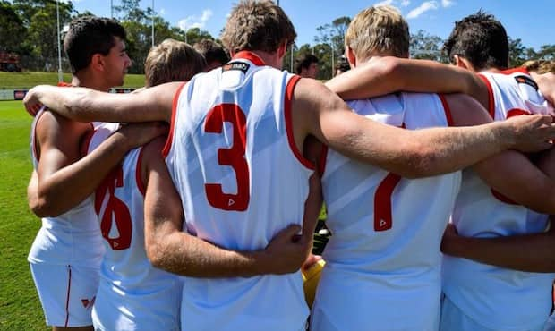 The QBE Sydney Swans Academy players huddle ahead of their clash against Brisbane.