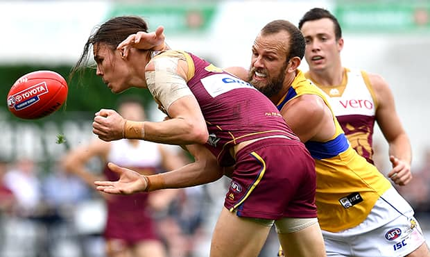 BRISBANE, AUSTRALIA - AUGUST 26:  Eric Hipwood of the Lions  is pressured by the defence of Will Schofield of the Eagles during the round 23 AFL match between the Brisbane Lions and the West Coast Eagles at The Gabba on August 26, 2018 in Brisbane, Australia.  (Photo by Bradley Kanaris/Getty Images/AFL Media)