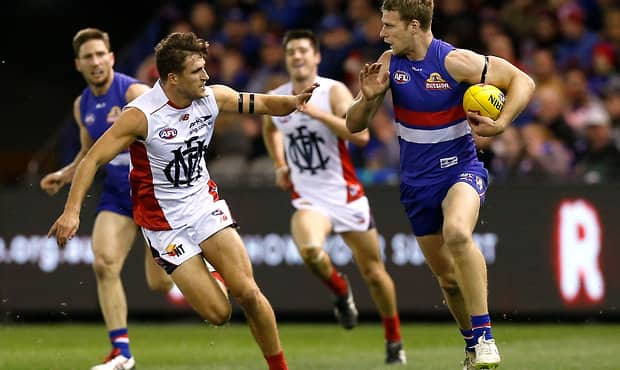 MELBOURNE, AUSTRALIA - AUGUST 16: Jake Stringer of the Bulldogs is chased by Viv Michie of the Demons during the 2015 AFL round 20 match between the Western Bulldogs and the Melbourne Demons at Etihad Stadium, Melbourne, Australia on August 16, 2015. (Photo by Adam Trafford/AFL Media)