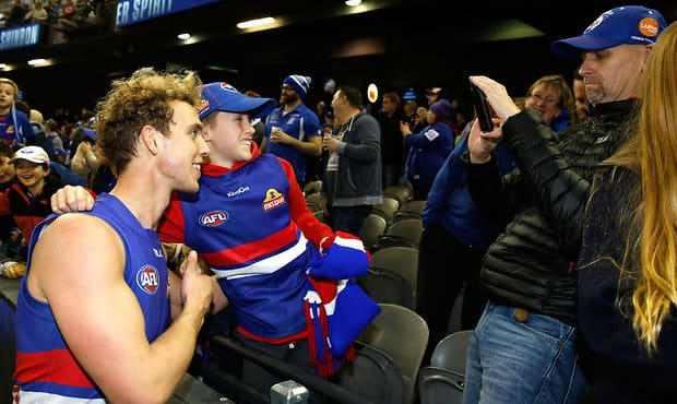 MELBOURNE, AUSTRALIA - AUGUST 29: Mitch Wallis of the Bulldogs poses for a selfie with a fan after the 2015 AFL round 22 match between the North Melbourne Kangaroos and the Western Bulldogs at Etihad Stadium, Melbourne, Australia on August 29, 2015. (Photo by Michael Willson/AFL Media)
