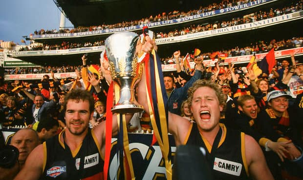 Mark Ricciuto and Kane Johnson holds up the Premiership Cup in front of the supporters after the 1998 AFL Grand Final between the North Melbourne and the Adelaide Crows at the Melbourne Cricket Ground.