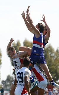 MELBOURNE, AUSTRALIA - MARCH 6: Tom Boyd of the Bulldogs takes a spectacular mark over Tom McDonald of the Demons during the 2016 NAB Challenge match between the Western Bulldogs and the Melbourne Demons at Highgate Recreational Reserve, Craigieburn on March 6, 2016. (Photo by Michael Willson/AFL Media)