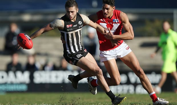 ADELAIDE, AUSTRALIA - AUGUST 7: R. Young of the Magpies is tackled by S. Tahana of the Roosters during the 2016 SANFL Round 19 match between Port Adelaide and North at Prospect Oval on August 7, 2016 in Adelaide, Australia. (Photo by James Elsby/AFL Media)
