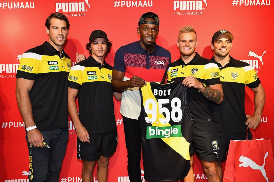 MELBOURNE, AUSTRALIA - FEBRUARY 07:  Alex Rance, Daniel Rioli, Brandon Ellis and Sam Lloyd of the Tigers present Usain Bolt of Jamaica with a guernsey during a Richmond Tigers AFL media opportunity at Melbourne Central Shopping Centre on February 7, 2017 in Melbourne, Australia.  (Photo by Quinn Rooney/Getty Images)