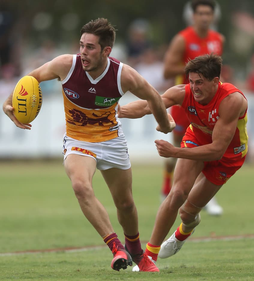 MERRIMAC, AUSTRALIA - FEBRUARY 19: Ryan Bastinac of the Lions breaks a tackle from David Swallow of the Suns during the AFL 2017JLT Community Series match between the Gold Coast Suns and the Brisbane Lions at Kombumerri Park on February 19, 2017 in Merrimac, Australia. (Photo by Sean Garnsworthy/AFL Media)