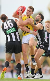 Richmond's Anthony Miles feels the pressure from two Magpies in Moe