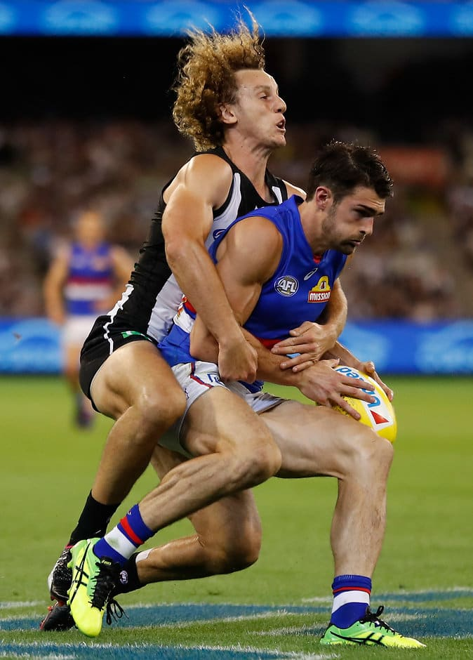 MELBOURNE, AUSTRALIA - MARCH 24: Easton Wood of the Bulldogs is tackled by Chris Mayne of the Magpies during the 2017 AFL round 01 match between the Collingwood Magpies and the Western Bulldogs at the Melbourne Cricket Ground on March 24, 2017 in Melbourne, Australia. (Photo by Michael Willson/AFL Media)