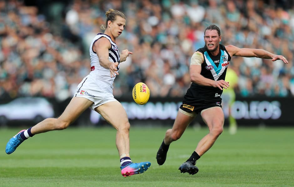 ADELAIDE, AUSTRALIA - APRIL 02: Nat Fyfe of the Dockers kicks past Brad Ebert of the Power during the 2017 AFL round 02 match between the Port Adelaide Power and the Fremantle Dockers at Adelaide Oval on April 02, 2017 in Adelaide, Australia. (Photo by AFL Media)