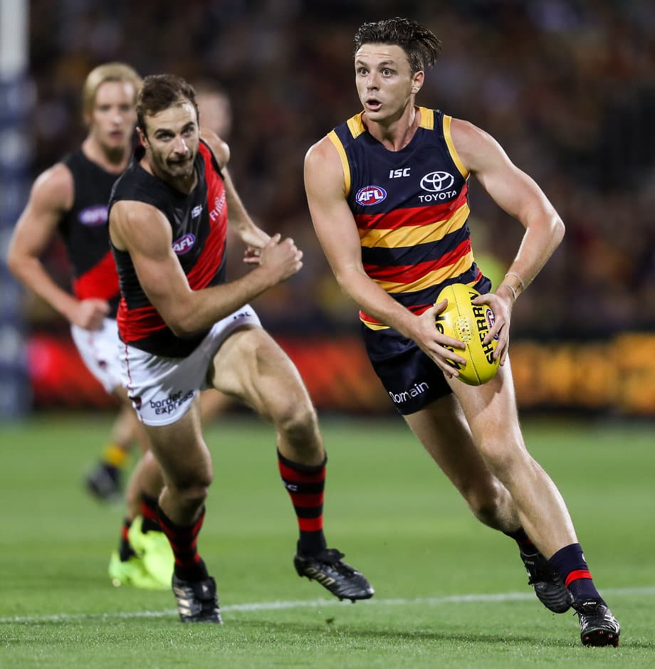 ADELAIDE, AUSTRALIA - APRIL 15: Jake Lever of the Crows breaks away from Jobe Watson of the Bombers during the 2017 AFL round 04 match between the Adelaide Crows and the Essendon Bombers at the Adelaide Oval on April 15, 2017 in Adelaide, Australia. (Photo by AFL Media)