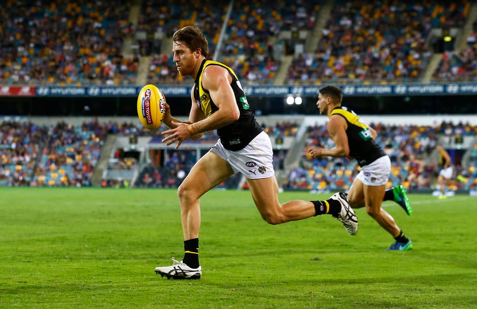 BRISBANE, AUSTRALIA - APRIL 16: Reece Conca of the Tigers runs with the ball during the 2017 AFL round 04 match between the Brisbane Lions and the Richmond Tigers at the Gabba on April 16, 2017 in Brisbane, Australia. (Photo by Jason O'Brien/AFL Media)
