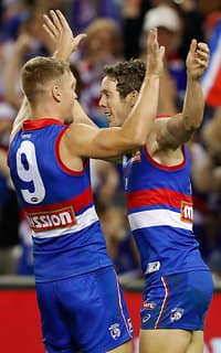 Robert Murphy celebrates a goal in his 300th game with Jake Stringer