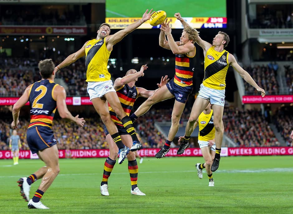ADELAIDE, AUSTRALIA - APRIL 30: Rory Sloane of the Crows marks between Toby Nankervis and Dylan Grimes of the Tigers during the 2017 AFL round 06 match between the Adelaide Crows and the Richmond Tigers at Adelaide Oval on April 30, 2017 in Adelaide, Australia. (Photo by AFL Media)