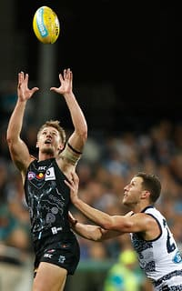 Port Adelaide's Hamish Hartlett and Geelong's Sam Menegola compete for the ball