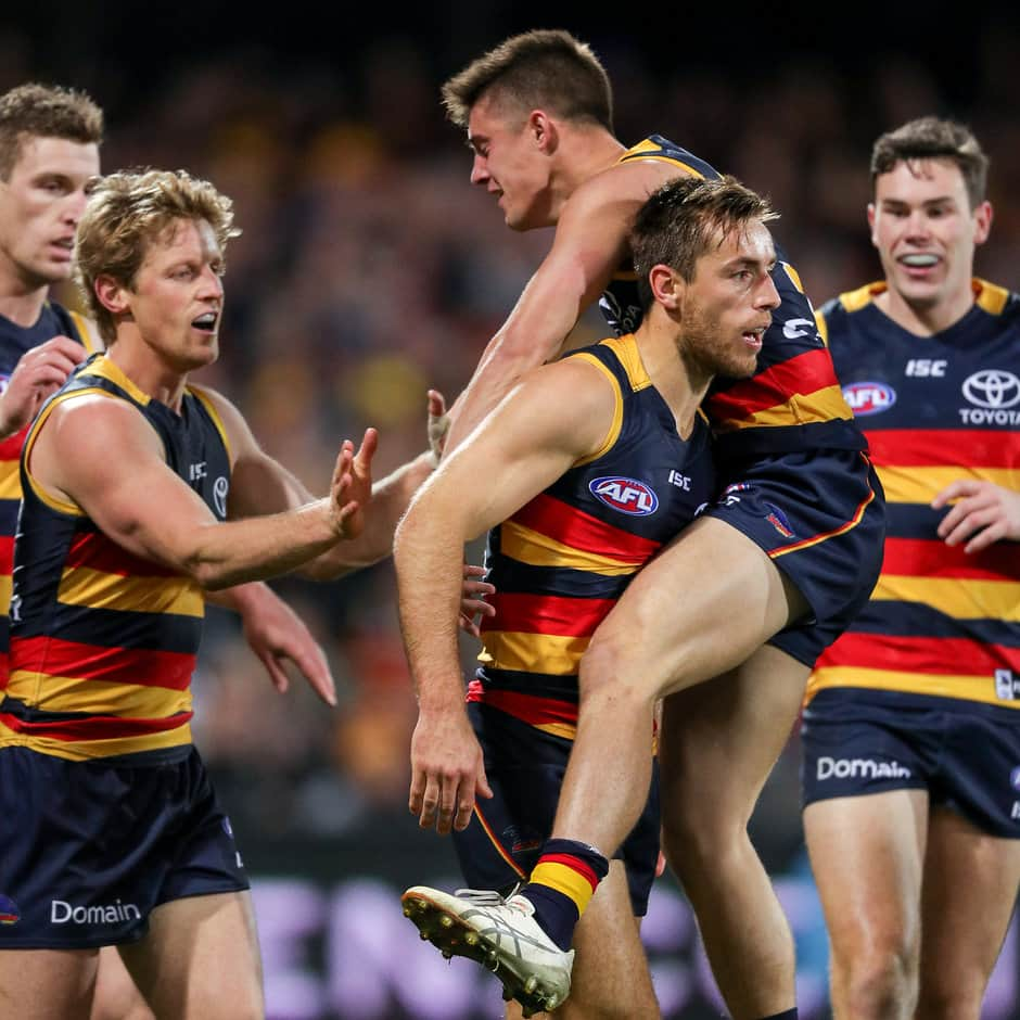 ADELAIDE, AUSTRALIA - JULY 21: Richard Douglas of the Crows celebrates a goal with team mates Rory Sloane, Riley Knight and Mitch McGovern during the 2017 AFL round 18 match between the Adelaide Crows and the Geelong Cats at the Adelaide Oval on July 21, 2017 in Adelaide, Australia. (Photo by AFL Media)