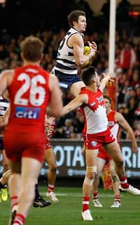 Patrick Dangerfield soars over Nic Newman for a stunning mark at the MCG