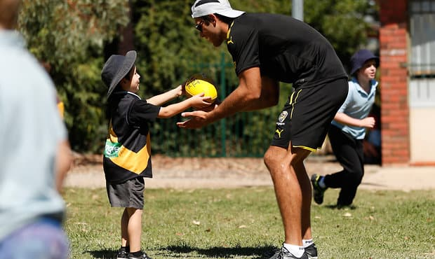 Alex Rance spends time with a student from Echuca Specialist School during Richmond's Community Camp