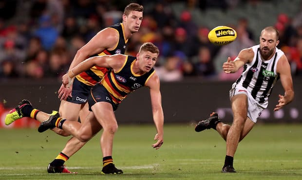ADELAIDE, AUSTRALIA - APRIL 13: Rory Laird of the Crows competes with Steele Sidebottom of the Magpies during the 2018 AFL Round 04 match between the Adelaide Crows and the Collingwood Magpies at Adelaide Oval on April 13, 2018 in Adelaide, Australia. (Photo by James Elsby/AFL Media)