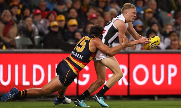 ADELAIDE, AUSTRALIA - APRIL 13: Jaidyn Stephenson of the Magpies is tackled by Kyle Hartigan of the Crows during the 2018 AFL Round 04 match between the Adelaide Crows and the Collingwood Magpies at Adelaide Oval on April 13, 2018 in Adelaide, Australia. (Photo by AFL Media)