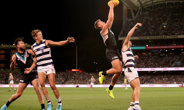 ADELAIDE, AUSTRALIA - APRIL 21: Ollie Wines of the Power flies over Joel Selwood of the Cats during the 2018 AFL round five match between the Port Adelaide Power and the Geelong Cats at Adelaide Oval on April 21, 2018 in Adelaide, Australia. (Photo by James Elsby/AFL Media)