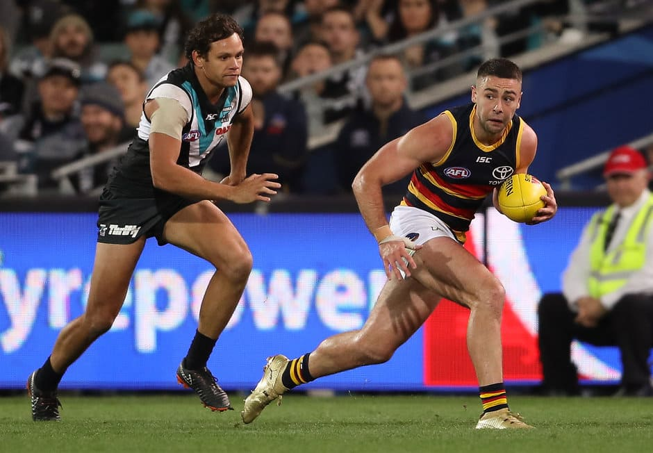 ADELAIDE, AUSTRALIA - MAY 12: Rory Atkins of the Crows being chased by Steven Motlop of the Power during the 2018 AFL round eight match between the Port Adelaide Power and the Adelaide Crows at Adelaide Oval on May 12, 2018 in Adelaide, Australia. (Photo by Matt Turner/AFL Media)