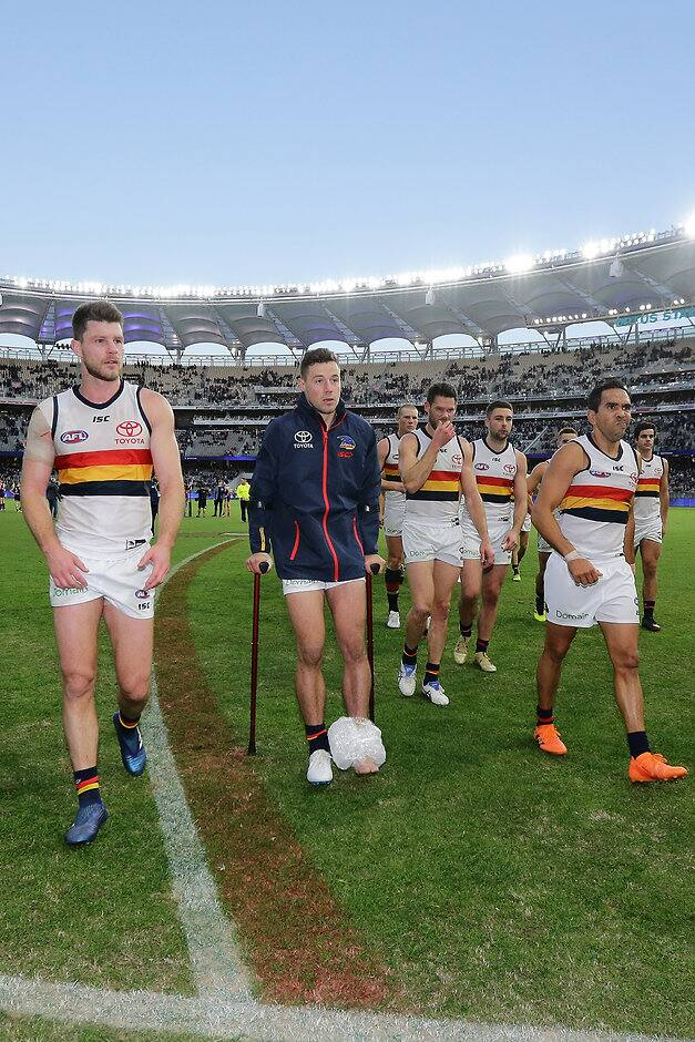 PERTH, AUSTRALIA - JUNE 10: Injured Luke Brown of the Crows leaves the field on crutches after the teams defeat during the 2018 AFL round 12 match between the Fremantle Dockers and the Adelaide Crows at Optus Stadium on June 10, 2018 in Perth, Australia. (Photo by Will Russell/AFL Media)