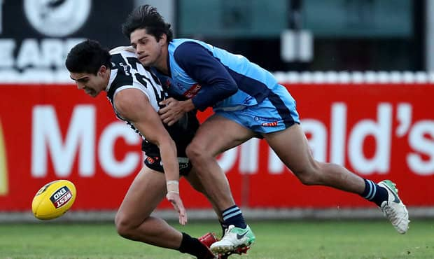 ADELAIDE, AUSTRALIA - June 17: Joel Garner of the Magpies is tackled by Shane McAdam of the Blues during the 2018 SANFL round 11 match between the Port Adelaide Magpies and the Sturt Football Club at Alberton Oval on June 17, 2018 in Adelaide, Australia. (Photo by James Elsby/AFL Media)